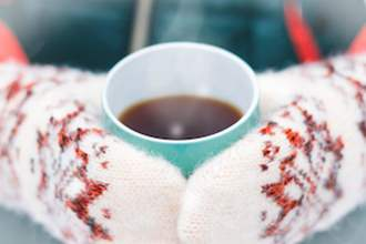 Hands in mittens holding a cup of coffee