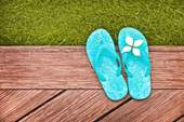 A pair of flip-flops on a backyard deck